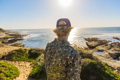 Young man standing, looking at ocean, rear view Stock Photos