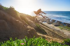 Young man jumping down sandy hill, in mid air Stock Photos