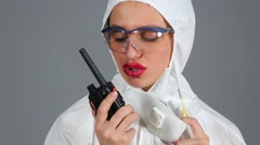 Girl in chemical protection strictly talking on a portable radio set Stock Footage