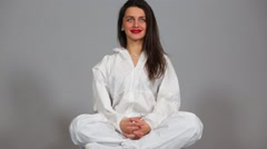Beautiful girl sitting in lotus pose dressed chemical protection Stock Footage