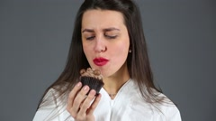 Beautiful girl with red lips gladly bites chocolate cupcake Stock Footage