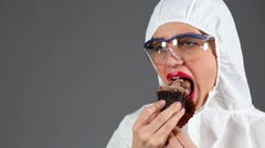 Beautiful girl in chemical protection suit eats chocolate cupcake Stock Footage