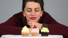Beautiful girl in red sweater with lust looking at three cupcakes Stock Footage
