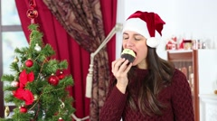 Beautiful girl in Santa Claus cap eats sweet cake with cream Stock Footage