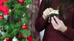 Girl in red sweater with pleasure eats sweet cake near Christmas tree Stock Footage