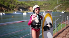 Little girl with wakeboard in lifejacket and helmet waves her hand Stock Footage