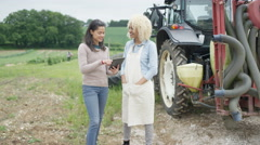 4K Portrait of smiling farm workers standing by tractor with computer tablet Stock Footage