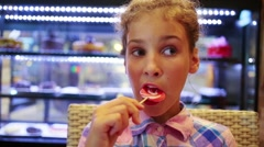 Little girl in shirt licking sweet lollipop at shop Stock Footage