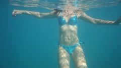 Beautiful girl in swimsuit swim under water at the sea Stock Footage