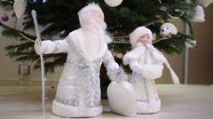 Toy of Santa Claus and Snow Maiden are standing near christmas tree. Stock Footage