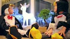 Two little boys in a penguin costume are sitting near deer and tree Stock Footage