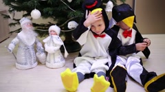 Two boys are sitting near fir, miniature of Ded Moroz and Snegurochka Stock Footage
