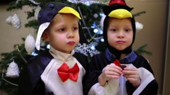 Two little boys in a penguin costume are standing near christmas tree Stock Footage