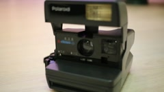A old fashioned camera polaroid is standing on the table. Stock Footage