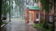 Bricks house with a lawn and trees under the rain at countryside. Stock Footage