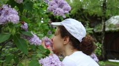 Young woman is smelling the branch of purple lilac. Stock Footage