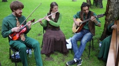 Four musicians are playing on their instruments at the park. Stock Footage