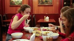 Mother with her children are sitting and eating soup at cafe. Stock Footage