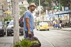 Two men, carrying travel bags,  looking for taxi Stock Photos