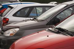 Cropped row of small cars in parking lot - stock photo