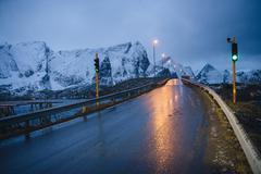 Wet highway and green light at dusk, Reine, Lofoten, Norway Stock Photos
