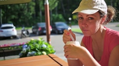 Woman is sitting at the table and eating ice cream on sunny day. Stock Footage