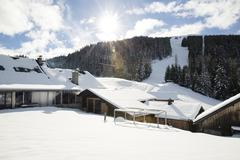 Snow holiday chalets in front of ski slope, Tyrol, Austria - stock photo