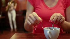 Young woman is holding pocketed tea and shake it in cup. Stock Footage