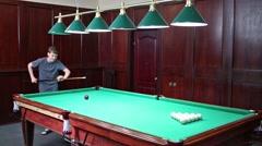 Little boy is breaking balls in a billiard under the lights. Stock Footage