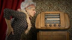 Funny grandmother turn on an old radio - stock footage