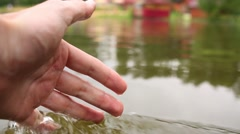 Man hand is touching the transparent water at lake. Stock Footage