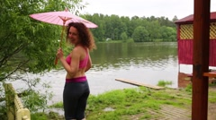 Young curly woman is standing under the umbrella near lake. Stock Footage