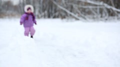 One little girl in purple jacket is walking on a snow at the park. Stock Footage