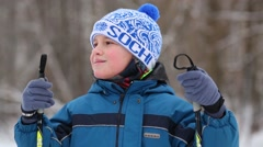 One boy in blue jacket is standing with sticks for skiing on the snow Stock Footage