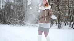 Young girl ice-skater is standing and throw up snow at park. Stock Footage