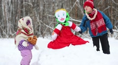 Two little children are standing near scarecrow for Maslenitsa Stock Footage