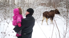 Father with daughter is standing and looking to elk eating branches Stock Footage