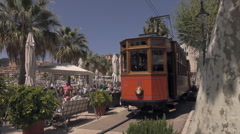 Soller railway runs past cafe in Port of Soller, Mallorca, Spain Stock Footage