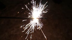 Person is holding burning stick of sparkler at night. Stock Footage