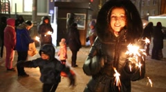 Woman is holding three burning sparklers in hand near crowd Stock Footage