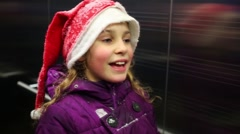 Girl is standing in elevator with santas cap and melting snow on it. Stock Footage
