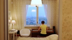 Reflection in mirror with back view of woman is playing on the piano Stock Footage