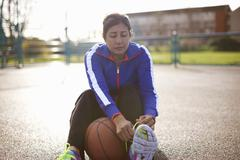 Mature female basketball player tying trainer laces Stock Photos