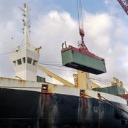 Shipping container being lowered by crane onto ship in port Stock Photos