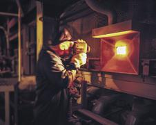 Worker measuring glass furnace temperature - stock photo