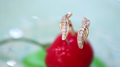 Womans golden earrings with zirconia in artificial cherry Stock Footage