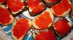 Bread with a butter and red caviar is laying on the plate Stock Footage