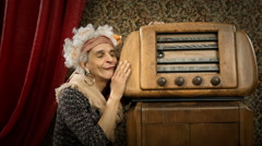 Funny grandmother is listening music to an old radio Stock Footage
