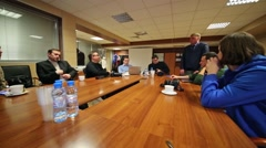 Bloggers are sitting at wooden table on meeting in Russian Post. Stock Footage