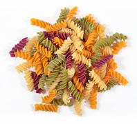 Heap of colored uncooked italian pasta fusilli on a white - stock photo